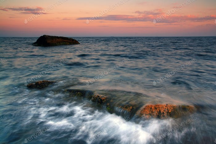 Sunset on the rocky shore of tropical sea