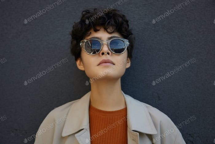 Close-up of attractive dark haired young curly female with short haircut wearing trendy sunglasses