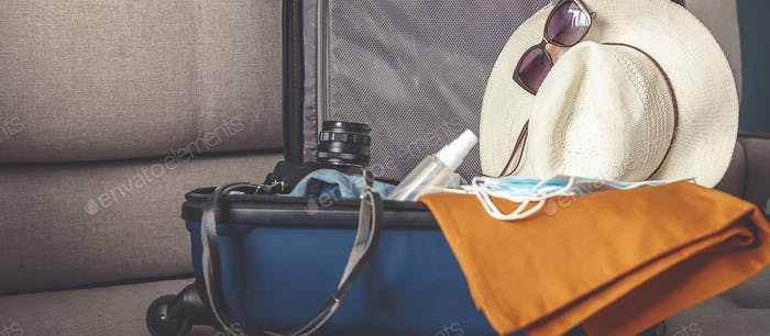 Travel. masked girl puts her things in a suitcase and dreams of rest, traveling after quarantine