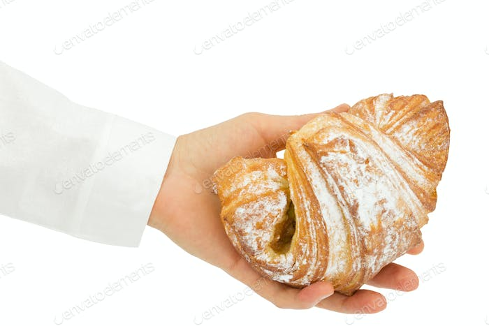 Baker holds a fresh bun  in the hands of, isolated on white back