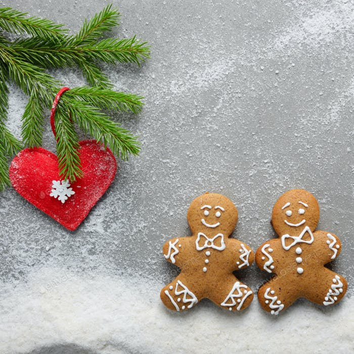 Flat lay at two gingerbread men having a walk on snow under fir