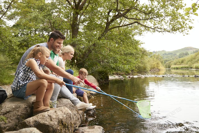 Family On Walk Fishing With Nets In River In UK Lake District