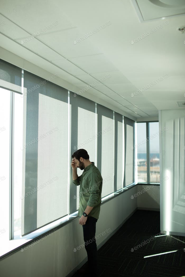 Worried business executive standing by window in office
