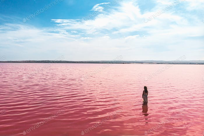 cute teenager girl wearing white dress in the water of an amazing pink lake