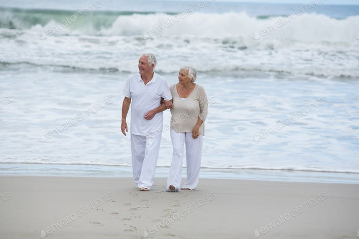 Seniorenpaar zu Fuß zusammen am Strand