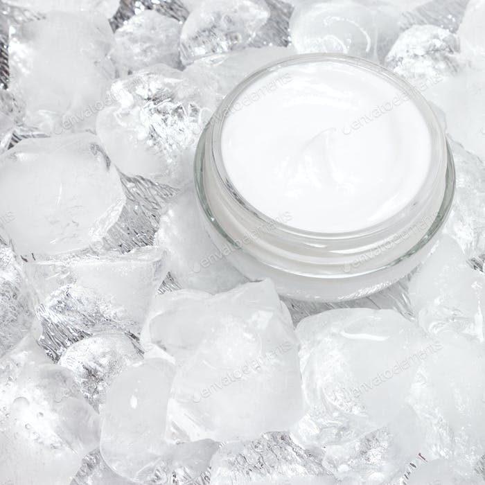 Close-up of open glass jar with cooling cream on crushed ice
