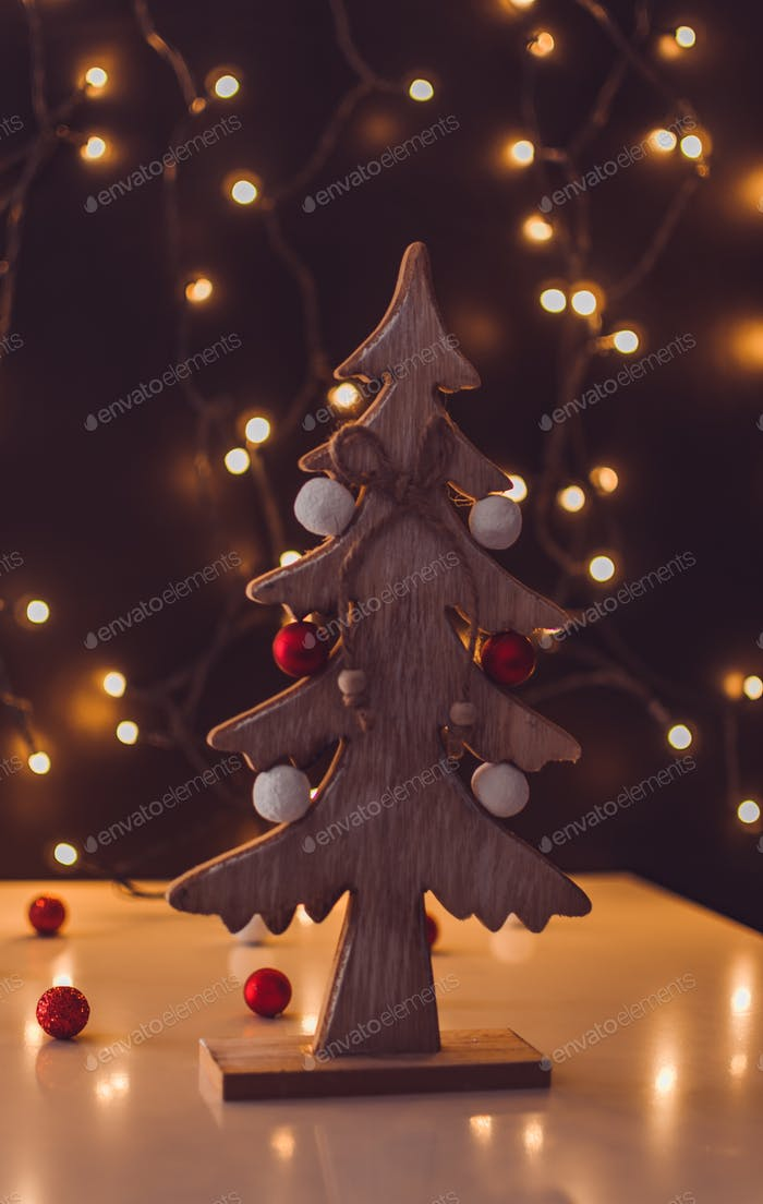 Kleiner hölzerner Weihnachtsbaum mit Bokeh Lichtern