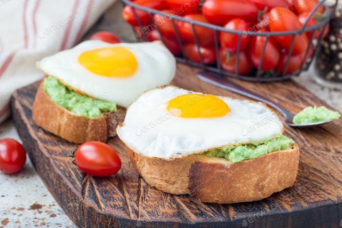 Open sandwich with mashed avocado and fried egg on toasted bread, horizontal