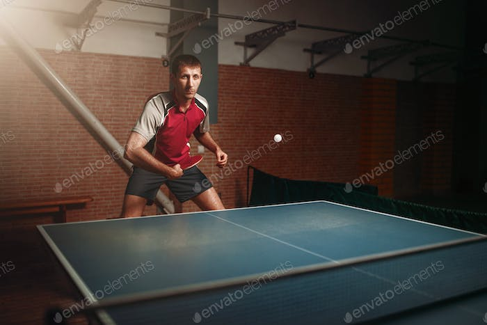 Man with racket in action, playing table tennis