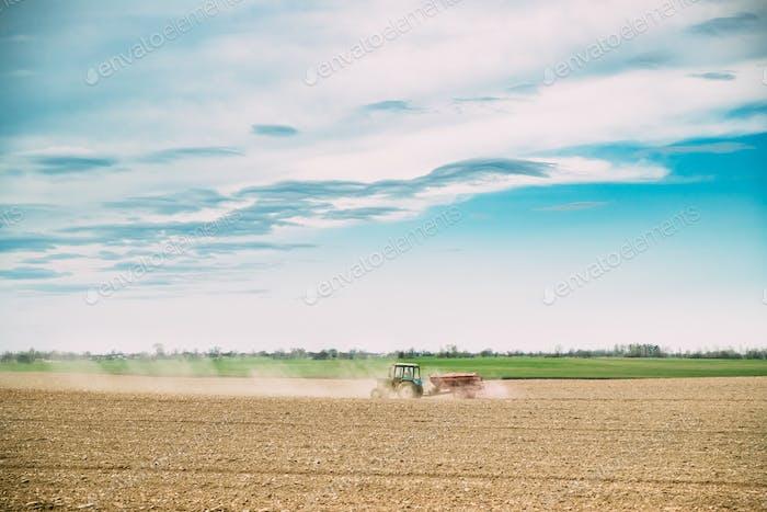 Traktor mit Sämaschine In Dusty Field In Spring Season. Anfang O