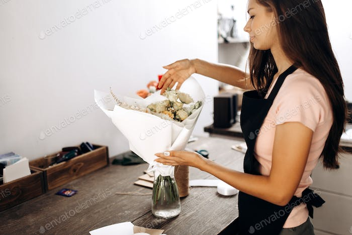 Florist touches bouquet of flowers in pastel colors packed in white paper is in a vase