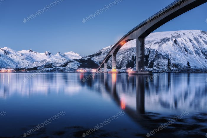 Bridge with illumination and snowy mountains at night