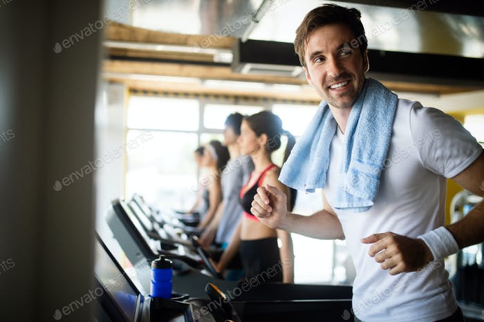 Happy fit people running on treadmill at fitness gym club