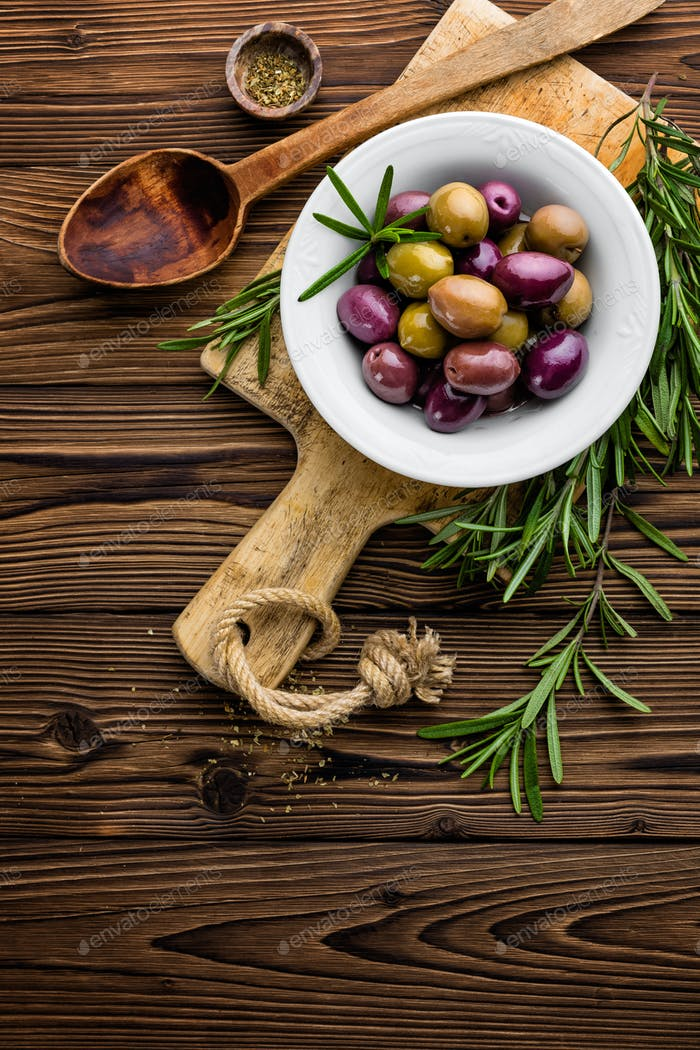 italian food ingredients, rosemary, olives, olive oil on wooden background