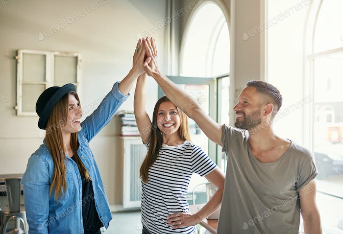 Three people standing and giving high five
