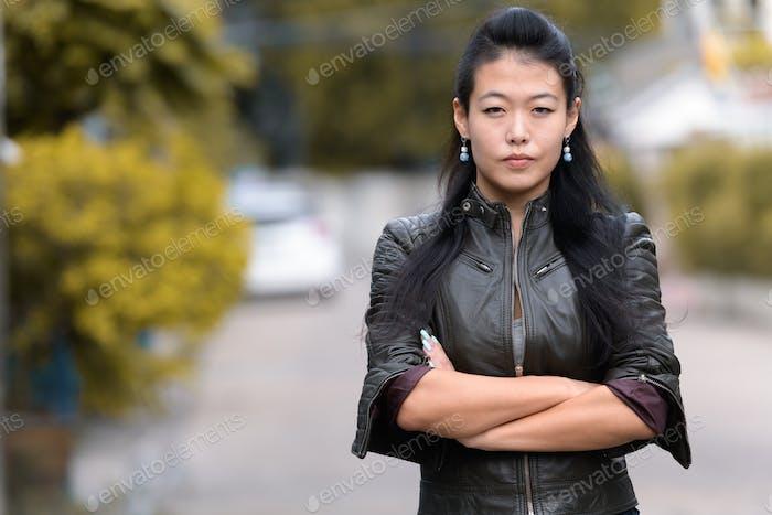 Porträt von schönen asiatischen rebellischen Frau mit Armen gekreuzt im freien