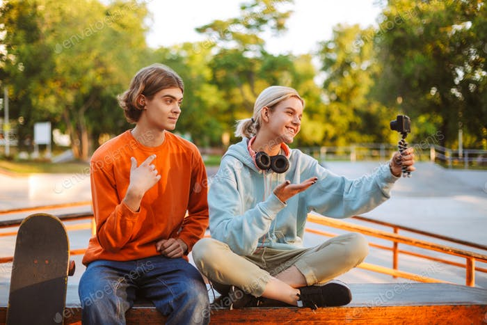 Young skater boy in orange pullover and girl with headphones rec