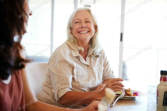 Senior white woman sitting at the family dinner table smiling to her adult daughter