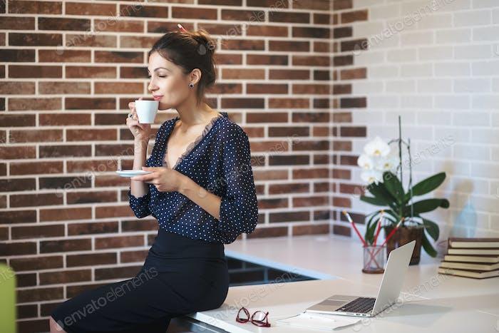 Business woman enjoying coffee aroma the office