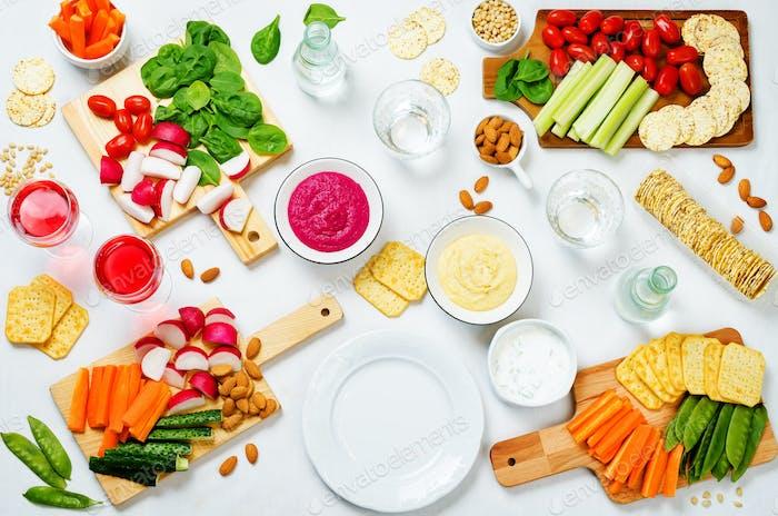 Variation von gesunden veganen Snacks. Gemüse, Cracker, Dip und Hummus