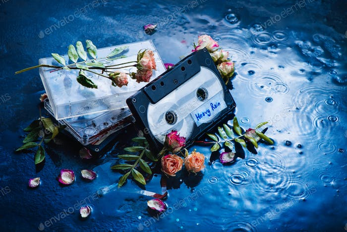 Audio cassette tape with Heavy Rain label in a scene with rose petals and raindrops. Melancholy