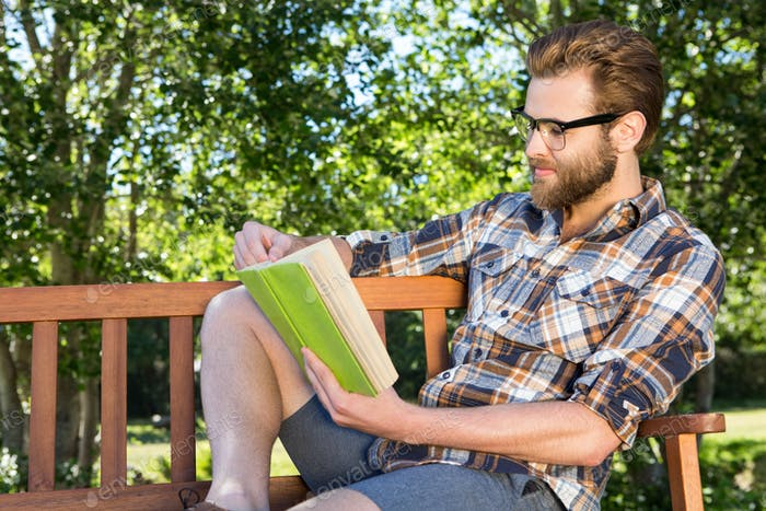 Handsome hipster reading in the park on a summers day