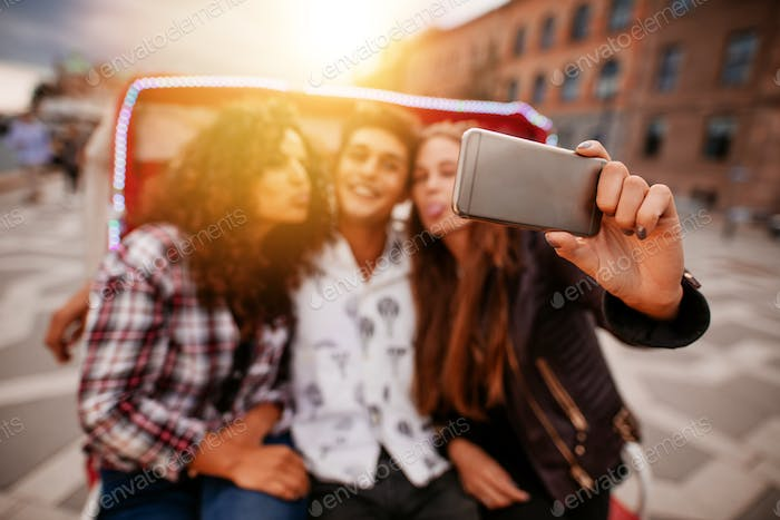 Young woman taking selfie on tricycle with friends