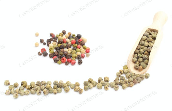 Heap of colored and green pepper on wooden spoon