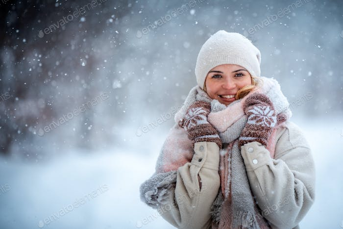 Winter portrait of young woman among snowy park