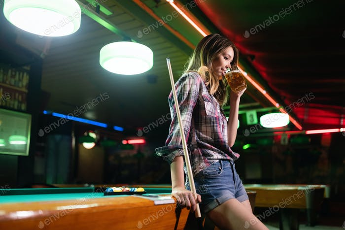 Young beautiful woman having fun and playing billiard in a club
