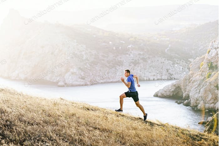 Mann Athlet läuft bergauf