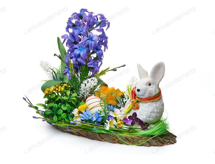 Osterinstallation aus einem Blumenarrangement und einem Kaninchen auf einem weißen Hintergrund