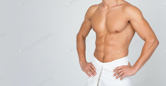 Closeup of man standing wrapped in towel at white studio