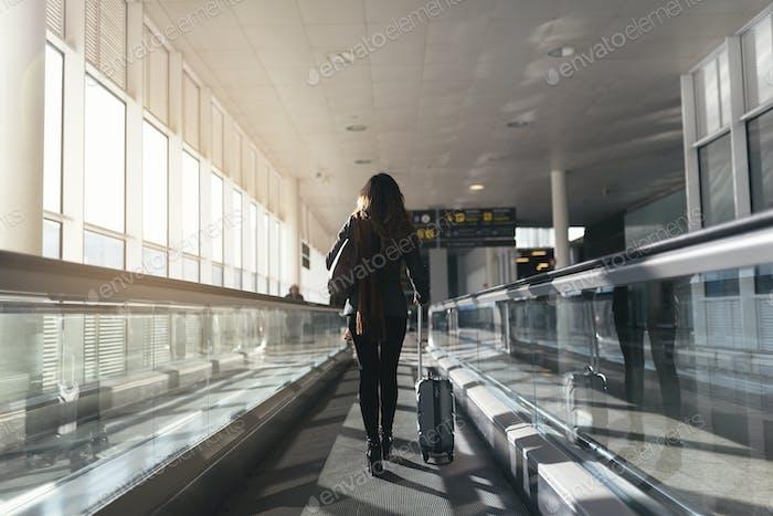 Mujer irreconocible caminando con maleta en el aeropuerto.