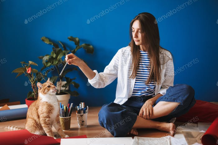 Thoughtful girl sitting on floor holding pencil while dreamily l