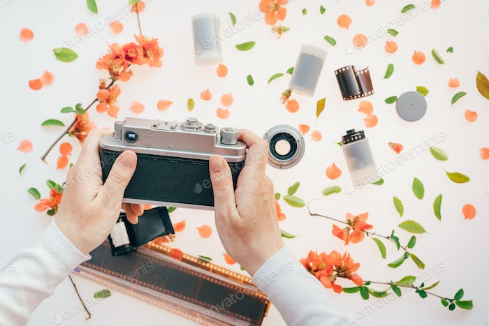 Woman holding vintage camera over springtime floral decoration