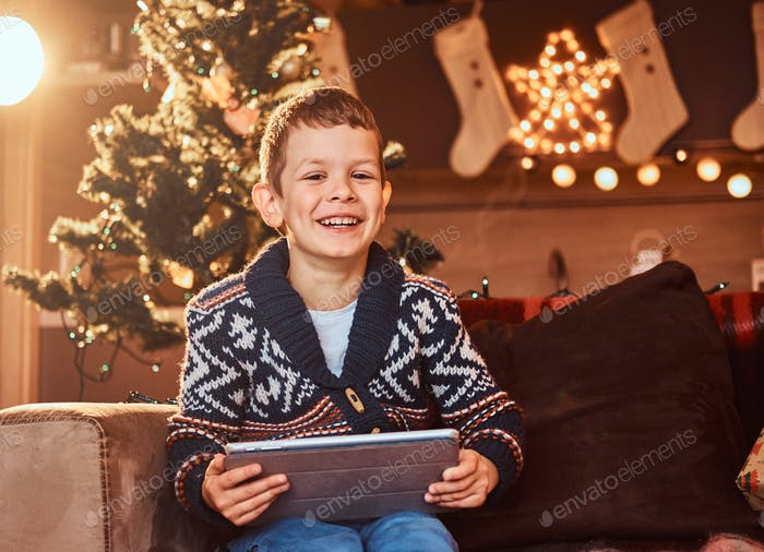 Happy cute boy in sweater sitting on a couch in decorated room at Christmas time.