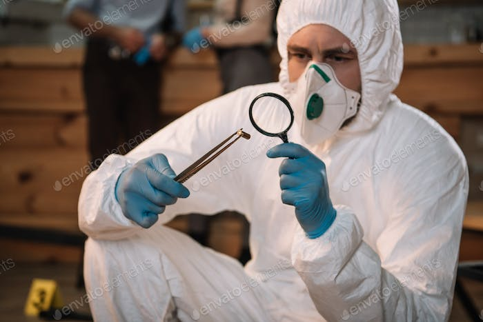 close up of forensic investigator examining evidence with magnifying glass at crime scene