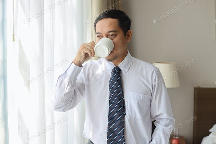 Asian businessman drinking coffee in the morning