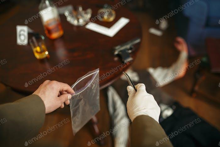 Männlicher Detektiv mit Pinzette sucht Beweise