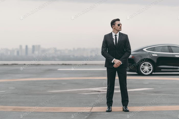 serious bodyguard standing with sunglasses and security earpiece on helipad and looking away