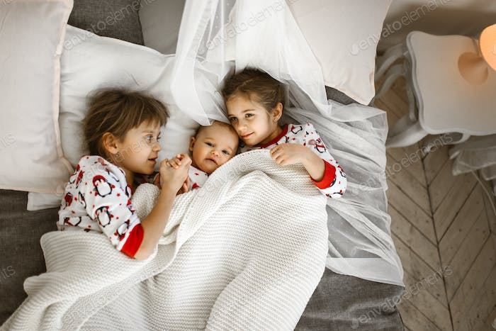 Two little sisters and a tiny brother lie on the bed under the white blanket in the light cozy