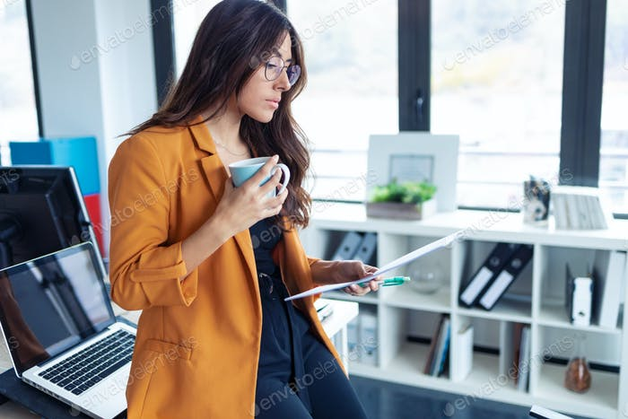 Business young woman drinking coffee while working in the office.