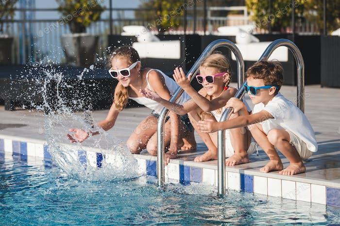 Drei glückliche Kinder sitzen in der Nähe von Schwimmbad am Tag Zeit.