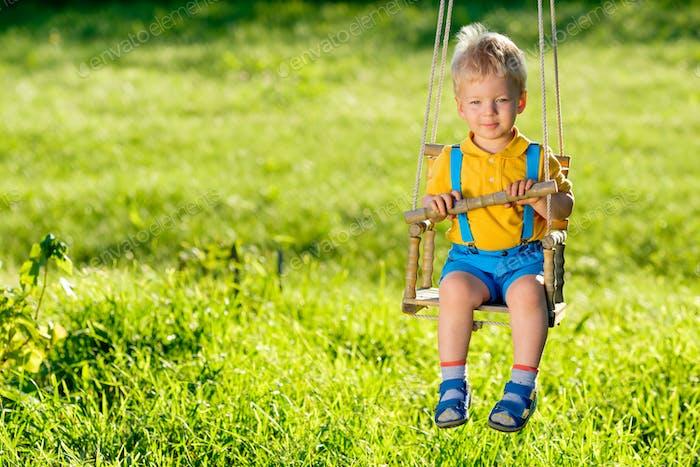 Ländliche Szene mit Kleinkind Jungen schwingen im Freien.