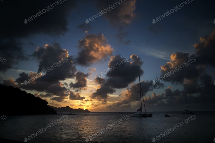 Sailingboat on the ocean under a cloudy sky at sunset.