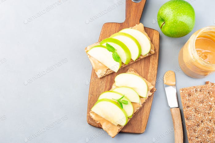 Sandwich with whole grain cracker, green apple slices and peanut butter