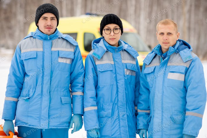 Brigade of three young paramedics in blue winter workwear and gloves