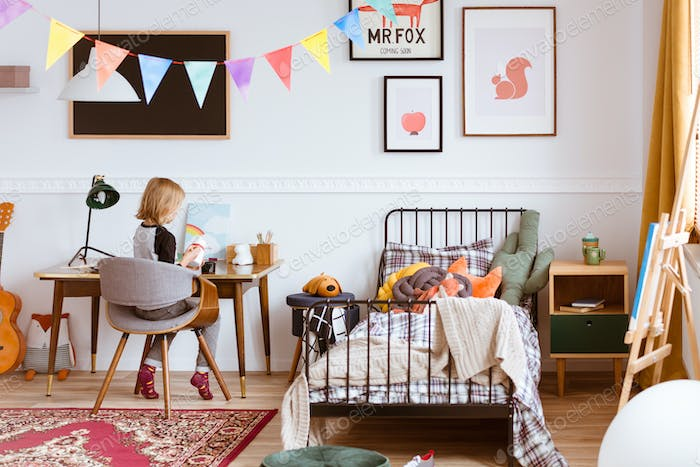Cute little girl sitting at desk in her stylish vintage bedroom with workspace
