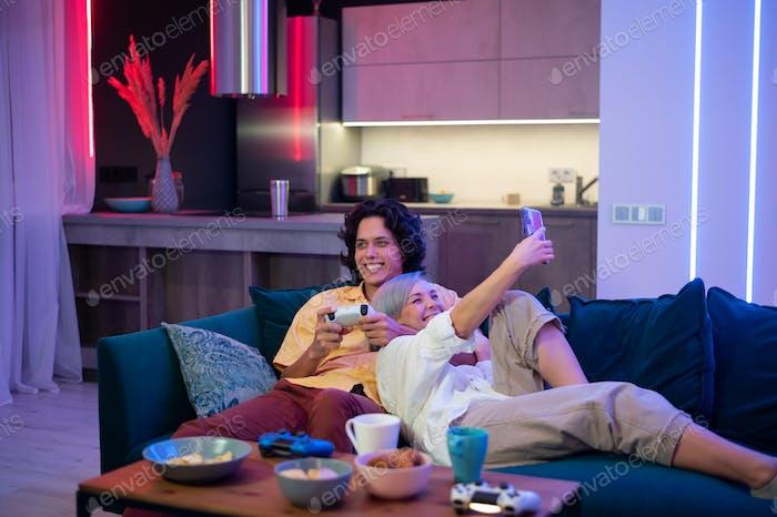 Kerl spielt Video spiel, während Mädchen Smartphone für soziale Medien benutzt. Zeit zusammen zu Hause  verbringen